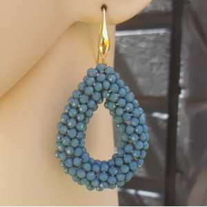 Goud vergulde oorbellen met open druppel van jeans blauwe kristallen