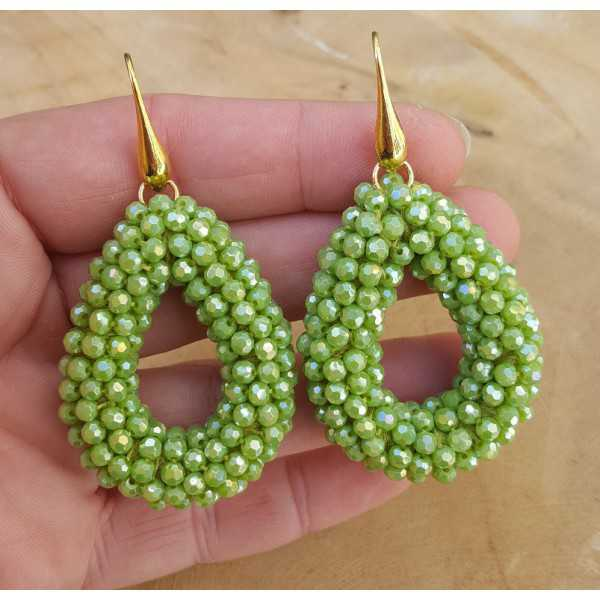 Gold plated earrings with open drop of green crystals