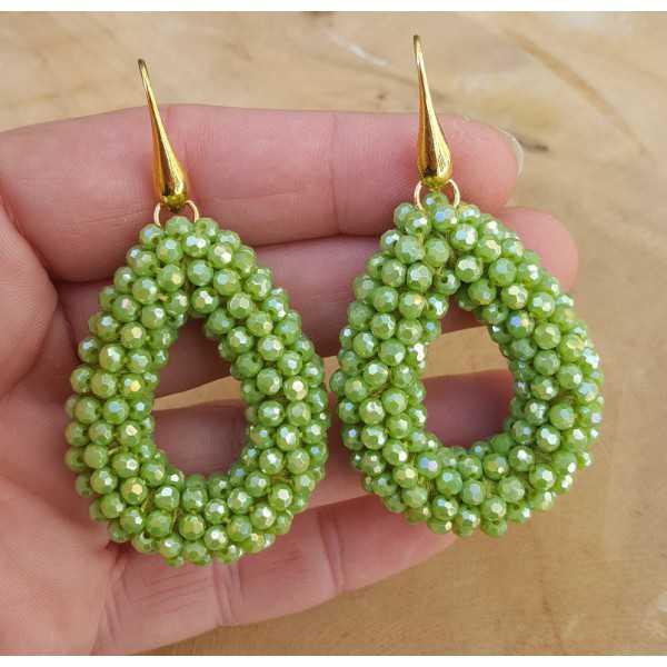 Goud vergulde oorbellen met open druppel van groen kristallen