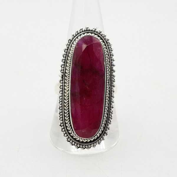 Ein silberner ring mit einem oval facettierten Rubin in