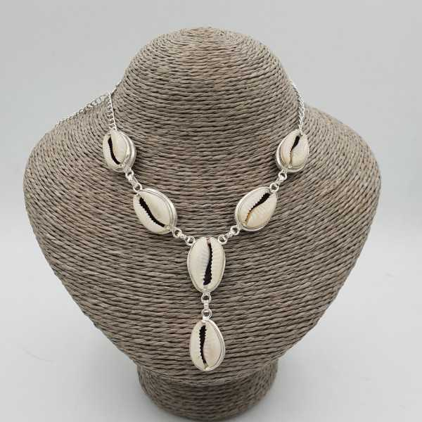 A silver necklace with a Cowrie shell